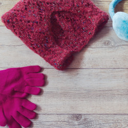 Winter clothes on wooden background. View from above with copy space